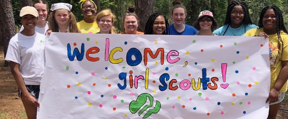 Girl Scouts holding a welcome to camp banner